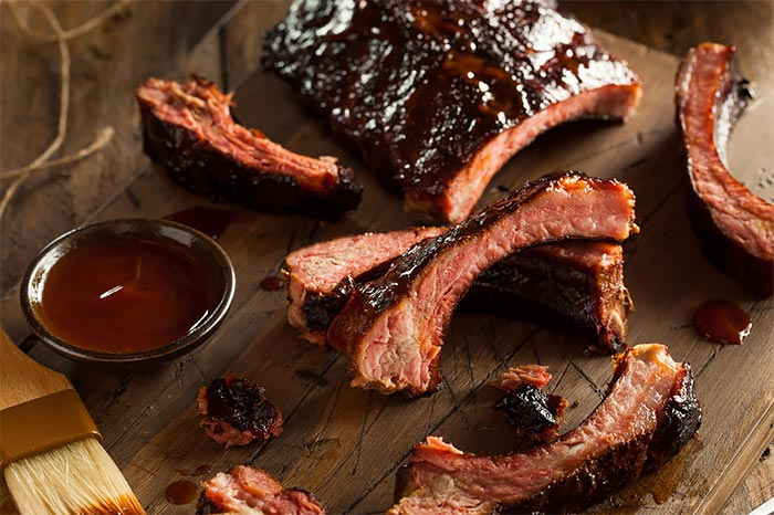 BBQ Ribs on a platter with a dipping dish of Lumberjack BBQ Sauce