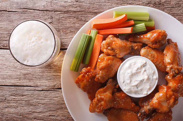 A plate of chicken wings made using Lumberjack wing sauce with celery and carrots, a dish of blue cheese and a beer