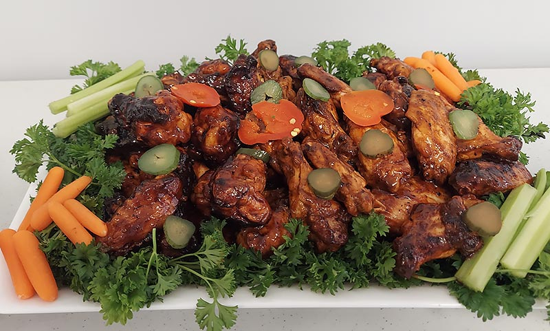 a large platter of barbecue chicken wings decorated with a variety of vegetables